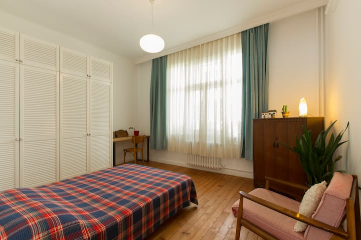 spacious & bright bedroom  double bed, wardrobe, desk and chair, armchair, big windows, wood flooring