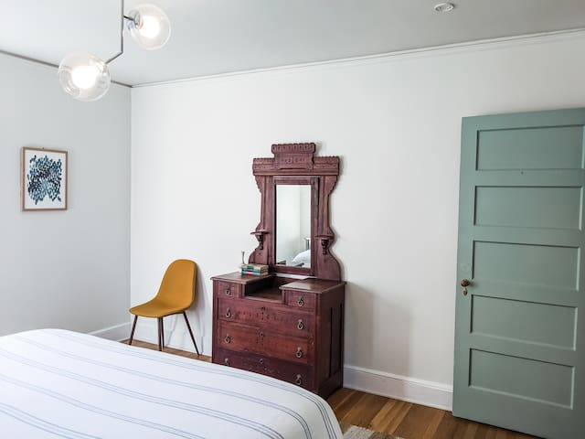 One of the two king bedrooms upstairs - gorgeous family heirloom hand carved bedroom vanity and new light fixture.