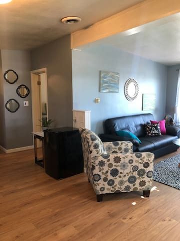 Open concept kitchen and living area. Mini fridge provided with water and a microwave.