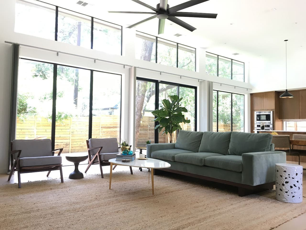 Bright, open-plan living area with floor to ceiling glass overlooking the private backyard and deck.