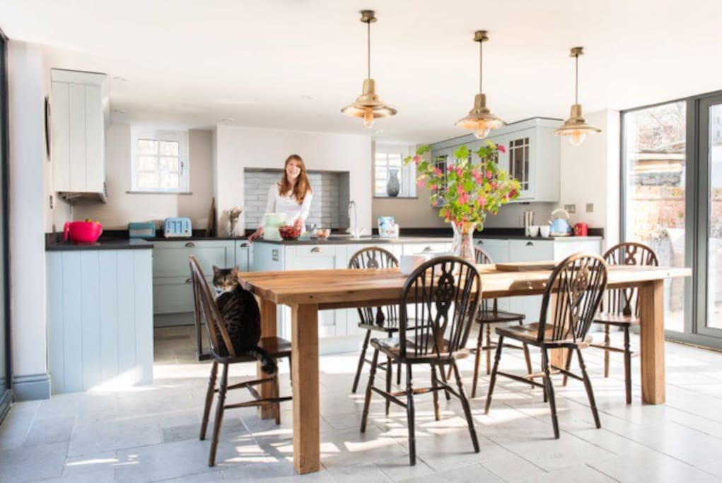 Spacious contemporary country kitchen with ample space to seat 10 round bespoke hand made rustic oak table.