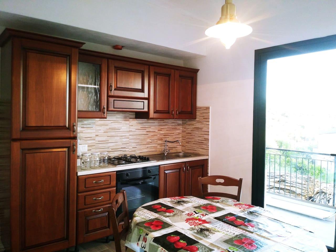 Salone con cucina attrezzata e finestrone panoramico.