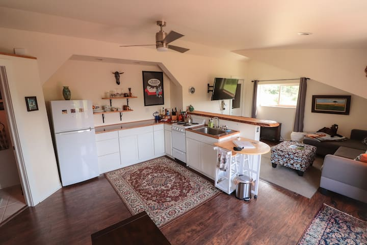Open kitchen with electric stove/oven, 3/4 sized fridge, and just about all cooking supplies you'd need to prepare a meal.