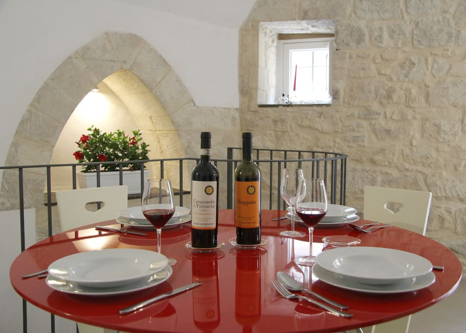 The bright dining room with our welcome: a bottle of our family wine