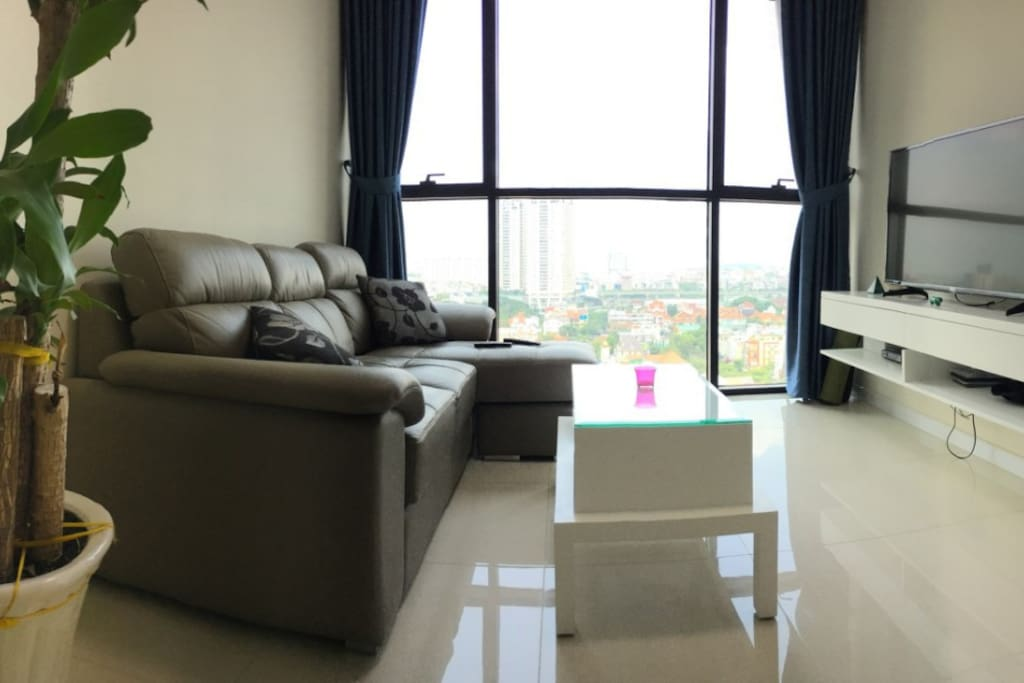 Spacious living room equipped with a comfy leather & lounge sofa, 48 inch smart & cable TV, coffee table and plant.