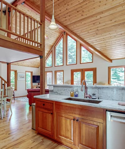Great Room: Light fills the room though picturesque windows. Pine paneled, cathedral ceilings, cable tv, wifi, wood burning stove, and a handmade glass chandelier make this space elegant, comfortable and cozy.