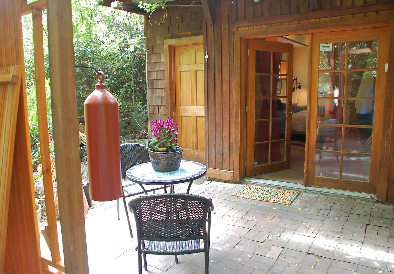 entrance to space thru double french doors & 200 sq ft brick patio. zen bell, bistro table under wisteria arbor