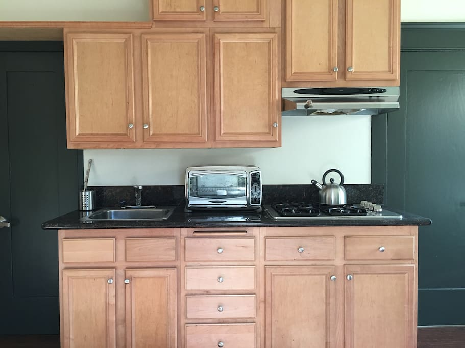 Freshly remodeled kitchen area with marble counters, stovetop, and toaster oven