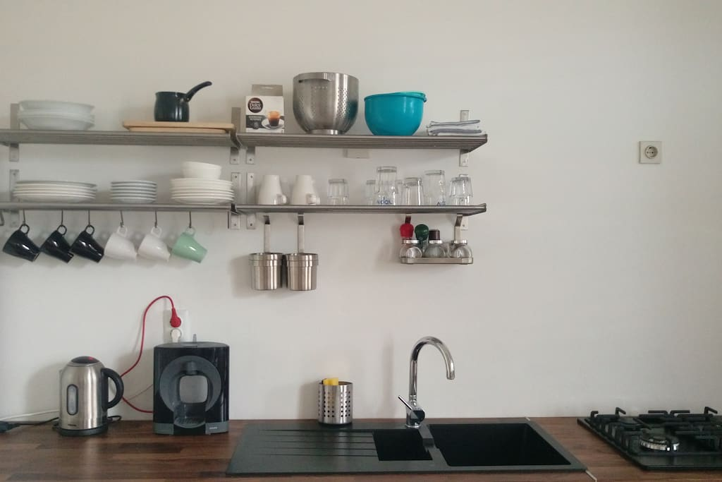 Fully equipped kitchen, with kitchenware, stovetops, and a coffee maker.