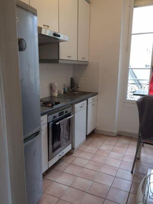 Cuisine équipée avec deux plaques électriques, un four à micro-ondes, un frigo et congélateur, une table et deux chaises hautes, vaisselle pour trois personnes