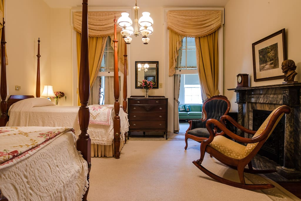 The back bedroom features two antique twin-sized beds -- original mantel, and other antique furnishings.