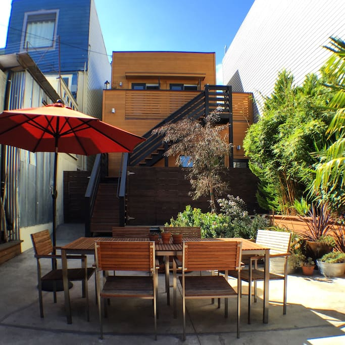 Patio dining & wood sided exterior of building.