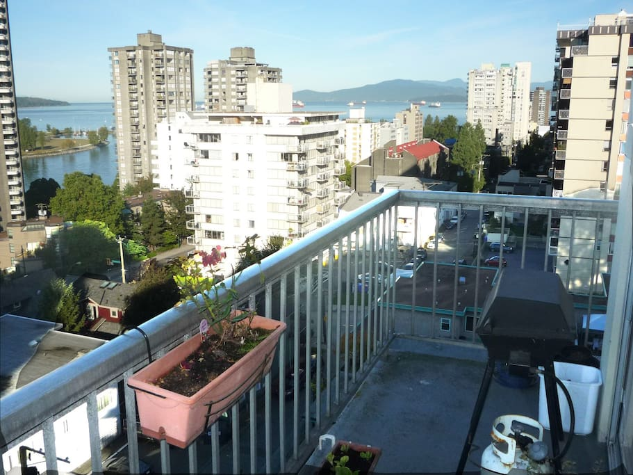 Daytime view of city and English Bay from balcony