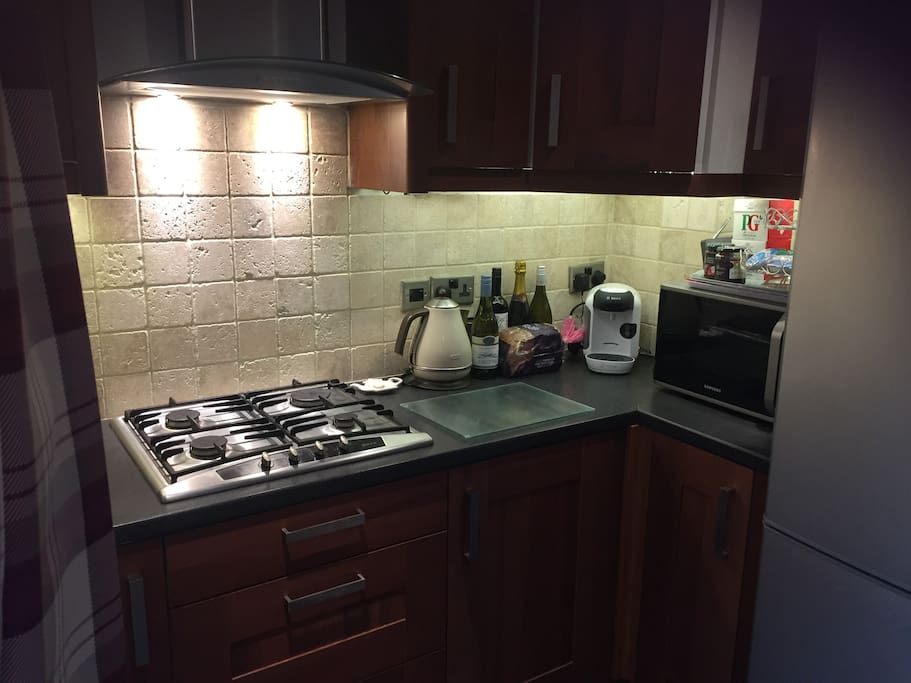 Kitchen with kettle, neff gas hob, microwave and toaster.