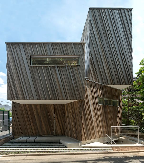 unique wooden box stacked house. Variouse left over woods attached in peculiar oblique design by artist, Kohei Nawa.