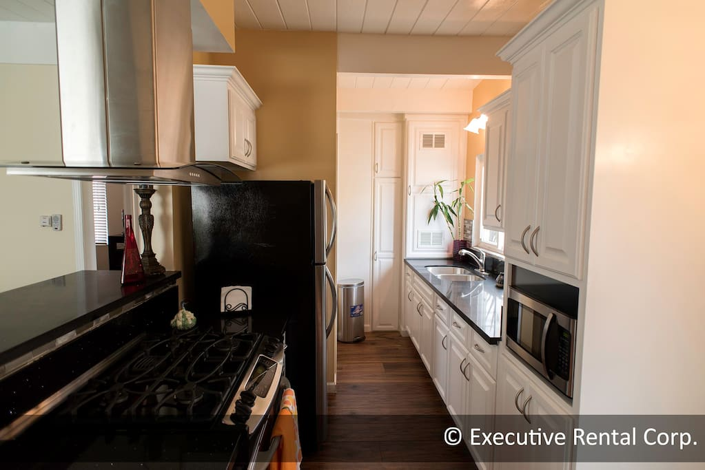 Kitchen with modern amenities; refrigerator, stove, microwave oven, sink