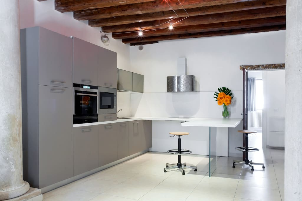 The table of the kitchen seems to be suspended but is above a glass plate , inside the kitchen , oven , microwave , fridge ,dishwasher,pots, pans, coffee espresso machine  and whashing machine