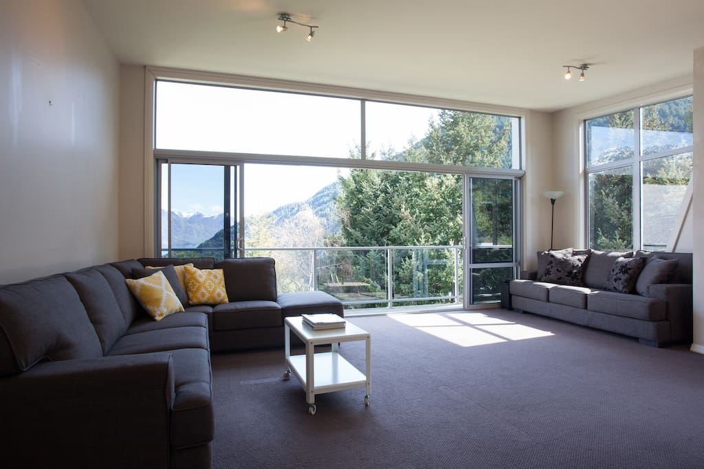 Open plan living with floor to ceiling windows to display a towering view of the mountains and Lake Wakatipu