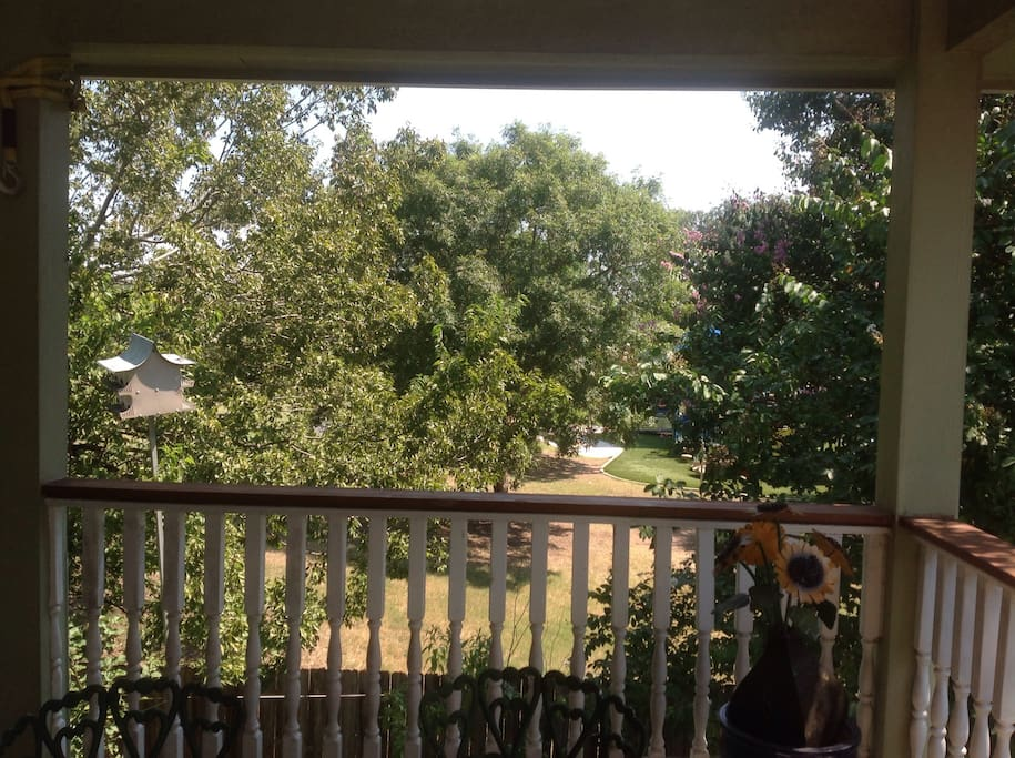 Upstairs covered balcony patio deck view nestled amongst surrounding trees.
