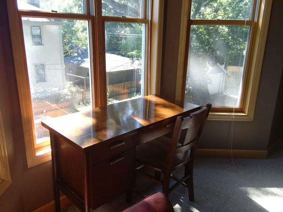 Sunny bay window with a desk for working.