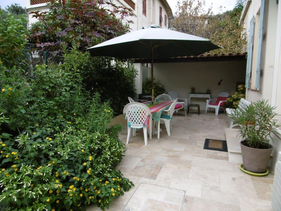Terrasse extérieure avec table et chaises et coin salon