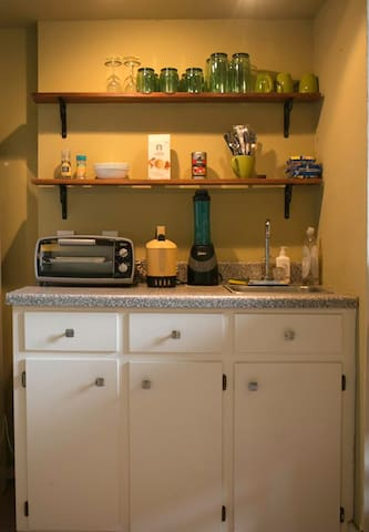 Kitchen area with refrigerator, coffee, microwave.
