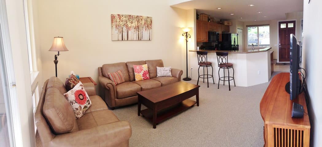 The open living room has vaulted ceilings and leather couches with a convertible coffee (to dining) table.