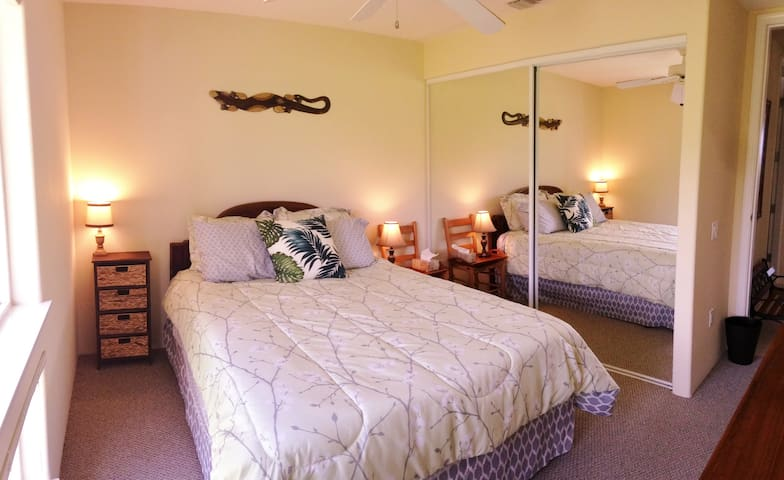 The second bedroom has a view of Hualalai Mountain and an extra large mirrored closet.