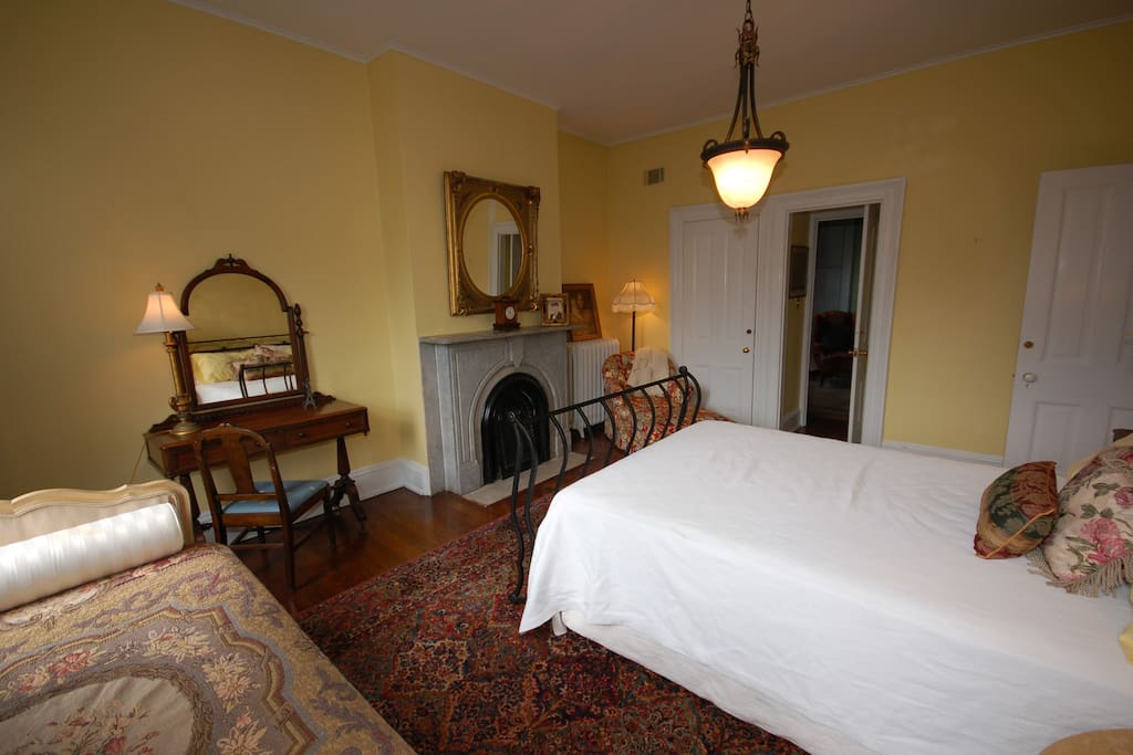 The room has a decorative fireplace and small desk