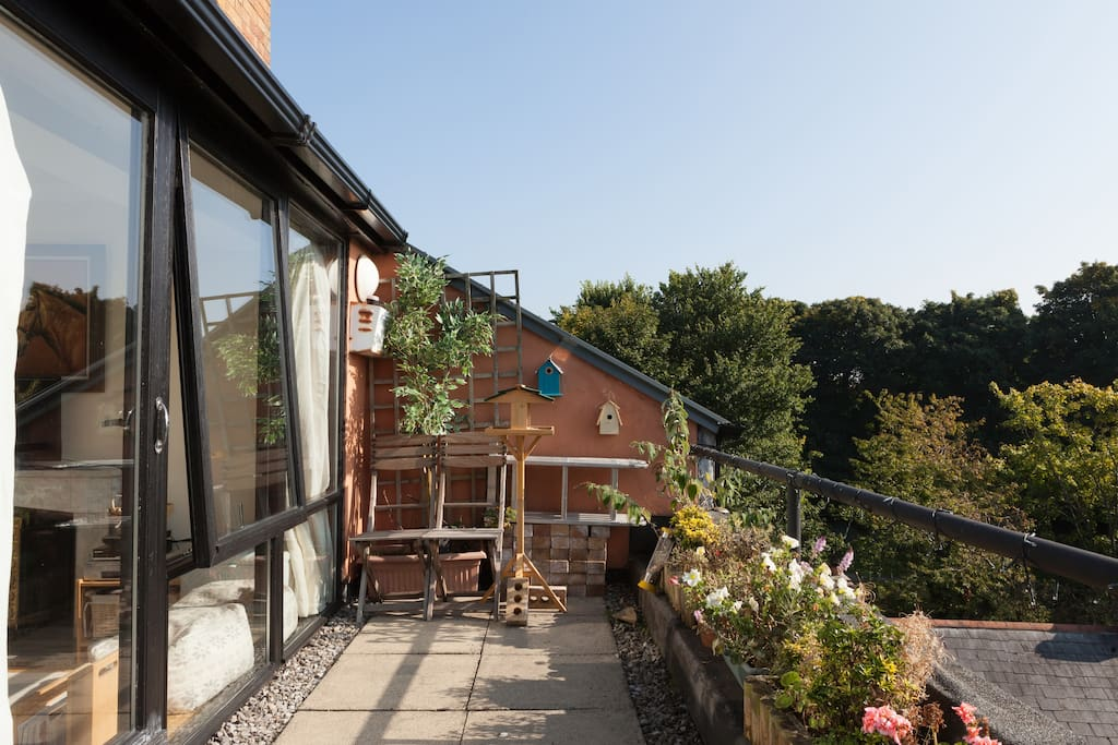 Flowers festoon the sun-drenched south-facing balcony which runs the length of the apartment