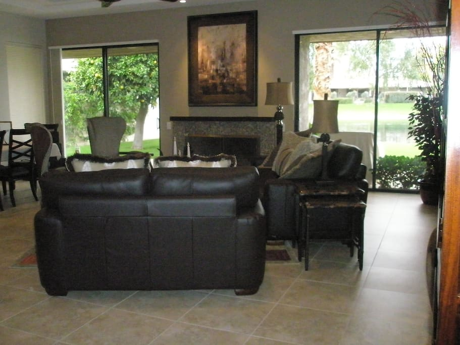 Living room of open concept with access to large patio and pond.