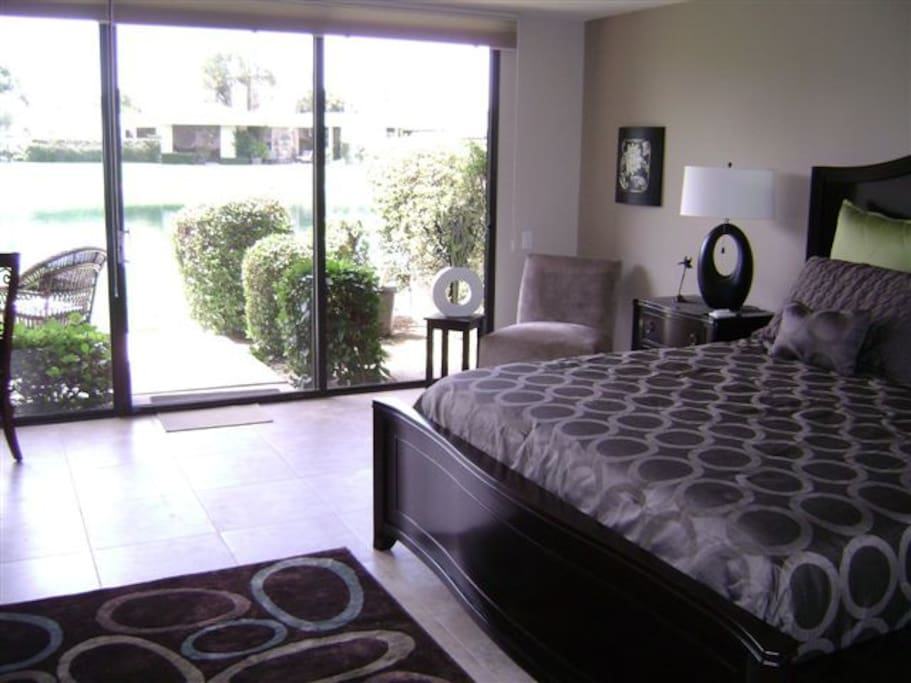 Master bedroom with King Bed access to large patio and view of mountains and pond.