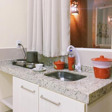 Possui mini-cozinha na suíte com kit básico com fogão elétrico e alguns itens como talheres, pratos e copos