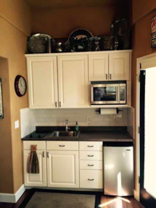 Kitchen with microwave, two burner cooktop and refrigerator.