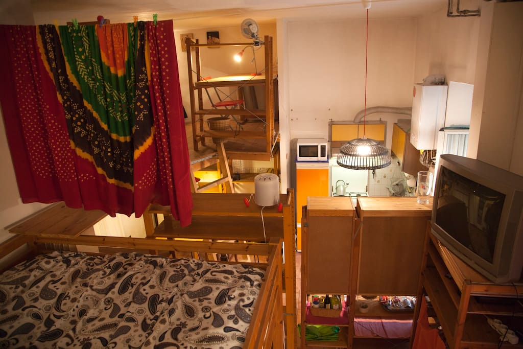 View of the studio from the double bed loft, pictured on the left.  The kitchen is visible on the right and the single bed loft area on the left behind the curtain.