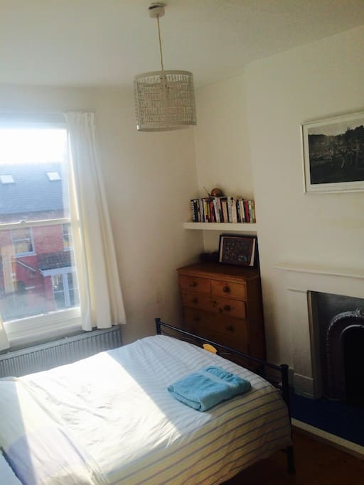 Sunny bedroom with comfortable double bed, wooden floors and fireplace