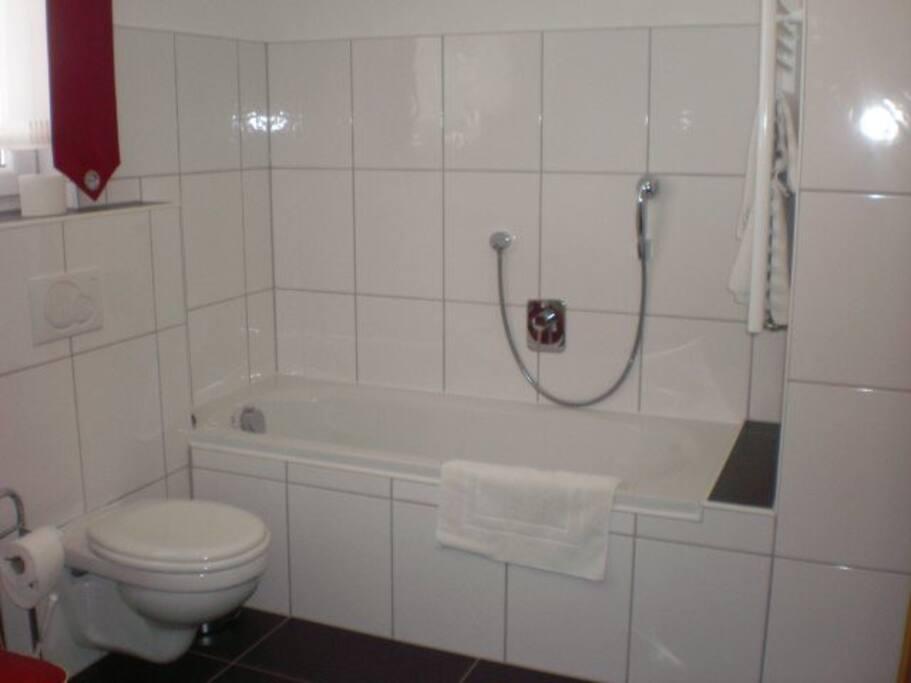 Das Badezimmer mit Badewanne, Dusche, WC