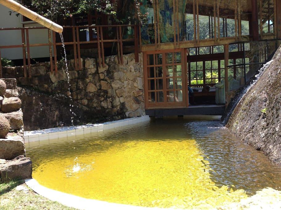 Casa apoiada na pedra com piscina de água natural sob a sala de lareira.
