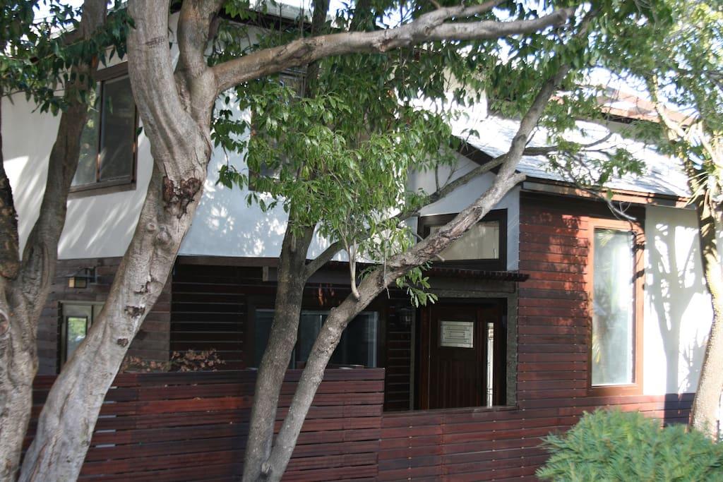 Ipe trellis and reclaimed granite ledgestone greet you at the front door