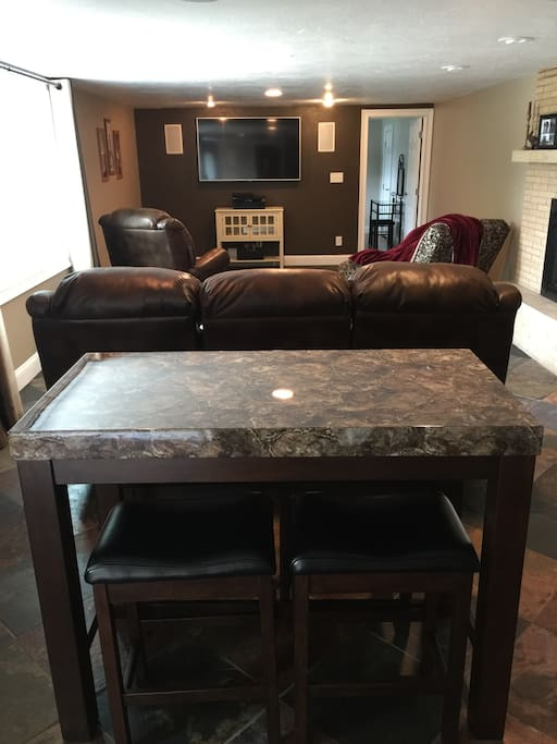 "60"" TV with surround sound in living area.  There is also a table in area."