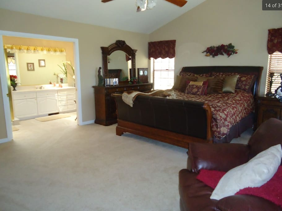 Master bedroom with king bed and sitting area overlooking lake
