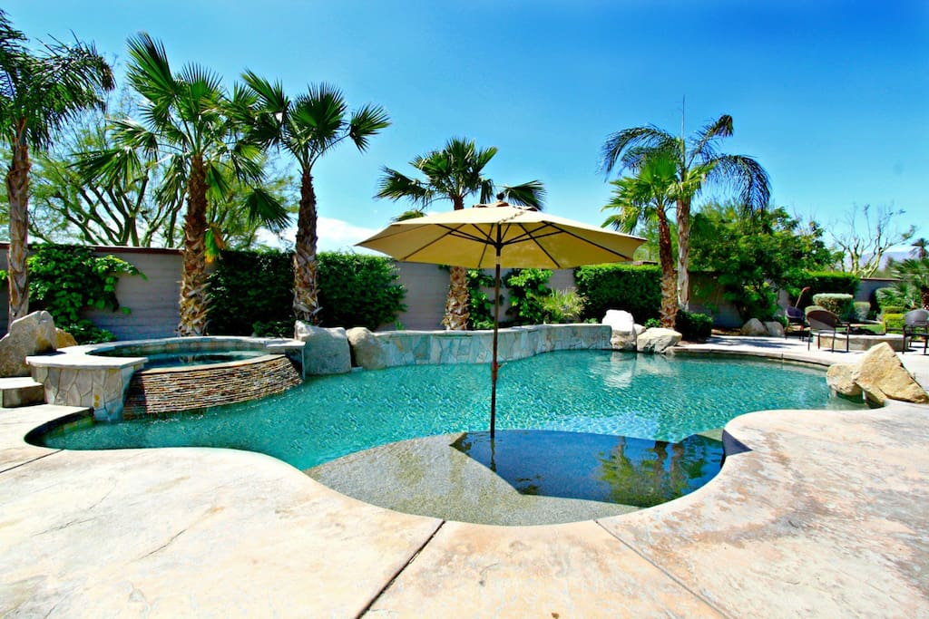 Heated saltwater pool with built-in tanning shelf, spa, and waterfall spillover