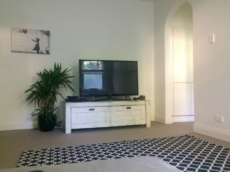 Living room area, L-shaped couch, Foxtel with sports and movies