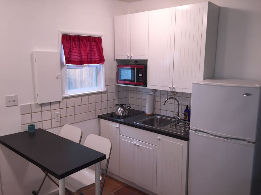 Our small but utilitarian kitchenette with stove, microwave, fridge, sink and eating area.