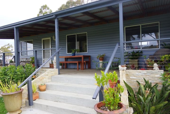 North-facing front deck, with comfy  chairs, BBQ and al fresco dining table and benches.