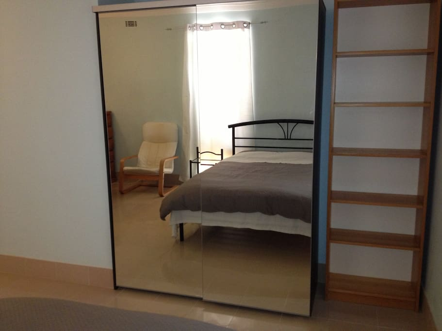 The room has large IKEA wardrobe for storage and the book case