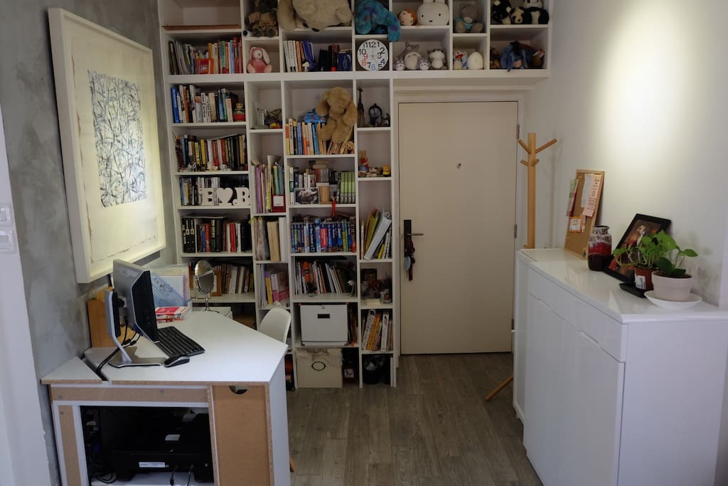 Entrance door, book shelf and study desk adjacent to living area