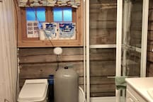 Bathroom with toilet, shower, washing machine and dryer