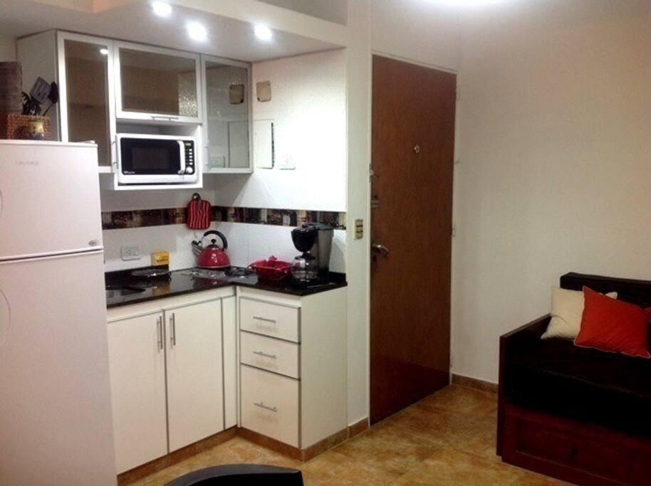 Living-comedor con cocina integrada. Divan-cama con 2 camas individuales. mesa y sillas para 5 personas. Heladera con freezer, anafe a gas, microondas, cafetera, tostador, utensilios para cocinar.
