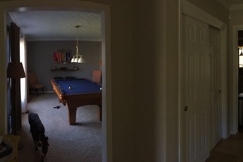 View of the game room, kitchen and stairway from the foyer.